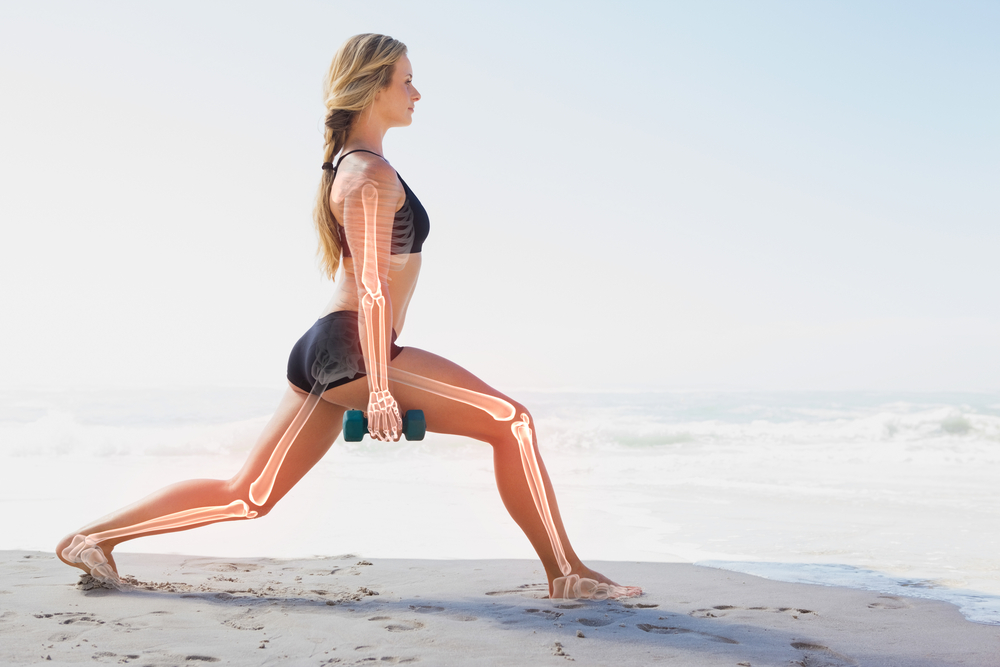 Digital composite of Highlighted bones of exercising woman